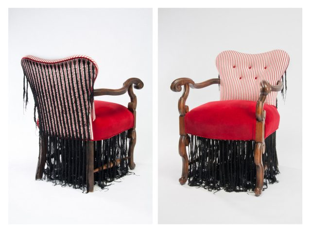 A sculpture of an arm chair with wooden legs and arms and a red fabric seat. Black cotton thread has been stitched onto the back and underside of the chair in the form of braided cornrows. The braids hand down beneath the chair, dangling to the ground.
