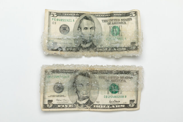 Two American five-dollar bills stacked on top of one another. Each one is half encased with crystalized sugar.