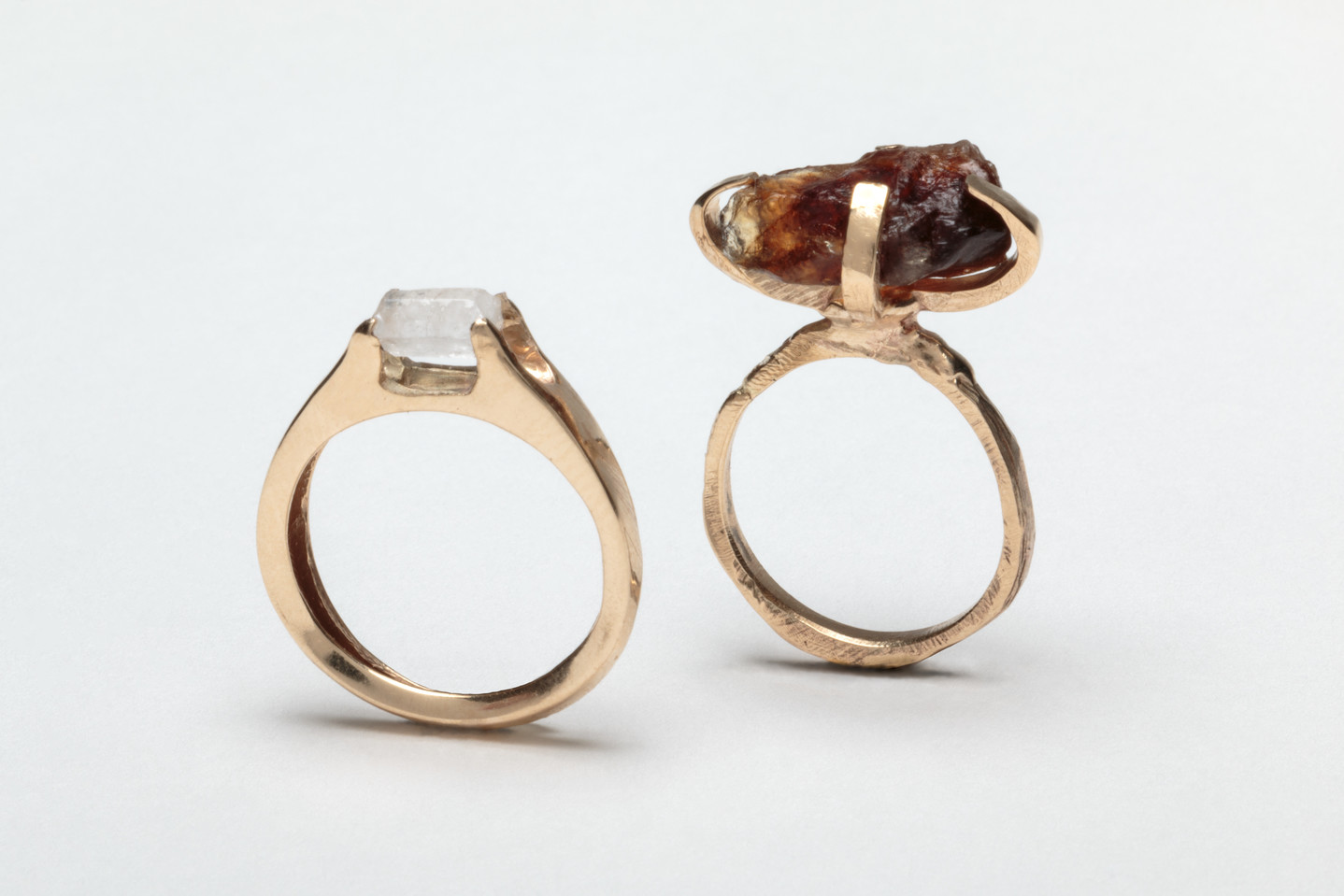 Two rings with gold bands and small gem-like forms on top. The gems are crafted from raw sugar. The left ring is perfectly circular with a small, white sugar crystal on top. The right ring is a slightly rougher circle, with a larger brown sugar crystal on top.