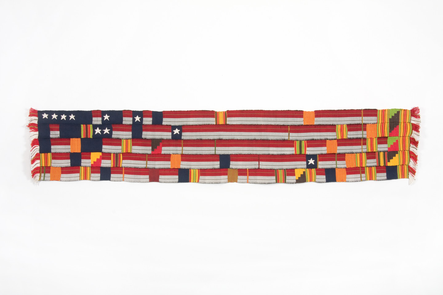 A horizontal, rectangular fabric artwork, made of woven strips of silk and cotton. The colors of the horizontal fabric strips are red, white, and blue, reminiscent of the American flag, while interwoven the vertical strips are shades of yellow, orange and green.