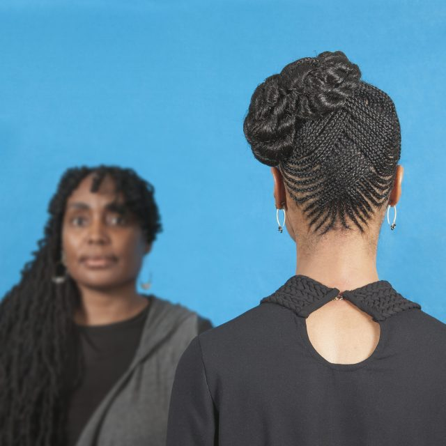 A color photograph featuring two dark skinned women in front of a blue background. The woman on the left has long brown hair pulled over her right shoulder. She is facing the camera and wears a black shirt with a grey cardigan. The woman on the right stands with her back to the camera wearing a black shirt with a single button at the top. Her brown hair is braided in an elaborate pattern and pulled up on the left side of her head.