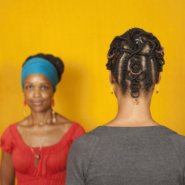 Two medium-dark skinned adult women stand in front of a goldenrod background. The woman on the left faces the viewer and wears a teal head wrap and a red top. The woman on the right faces away from the viewer, showcasing her dark hair braided into an elaborate pattern with colorful beads.