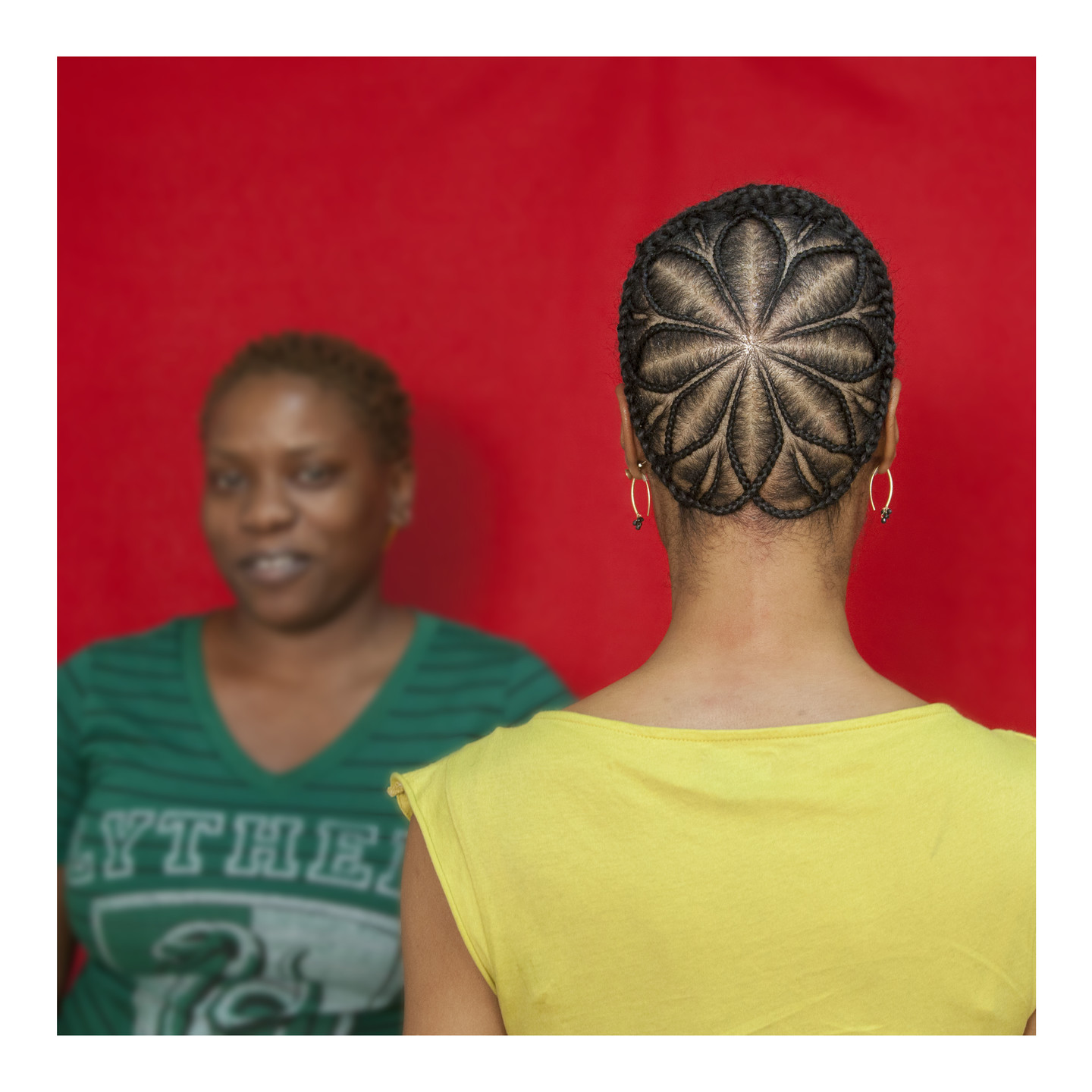 A color photograph featuring two dark skinned women in front of a red background. The woman on the left has very short brown hair and faces the camera, she is wearing a green v-neck t-shirt. The woman on the right stands with her back to the camera wearing a yellow shirt. Her brown hair is braided in an elaborate star pattern.