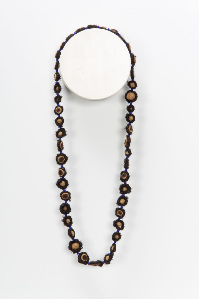 A necklace made from coiled, balled, and twisted dark human hair hangs on the wall. The hair is wrapped around small beads.