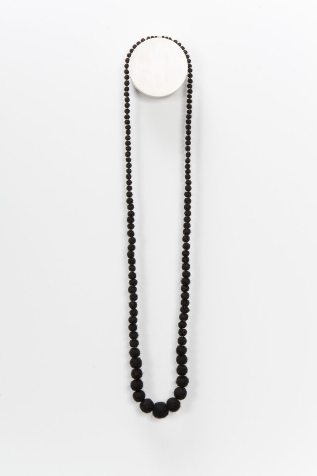 A necklace made from coiled, balled, and twisted dark human hair hangs on the wall. The hair is rolled into balls that grow in size toward the middle.