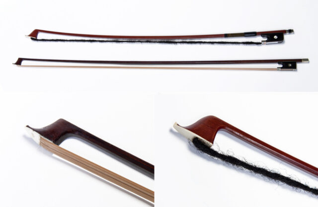 Two wooden violin bows, one strung with straight, smooth blond hair, and the other strung with a dark dreadlock, made from human hair.