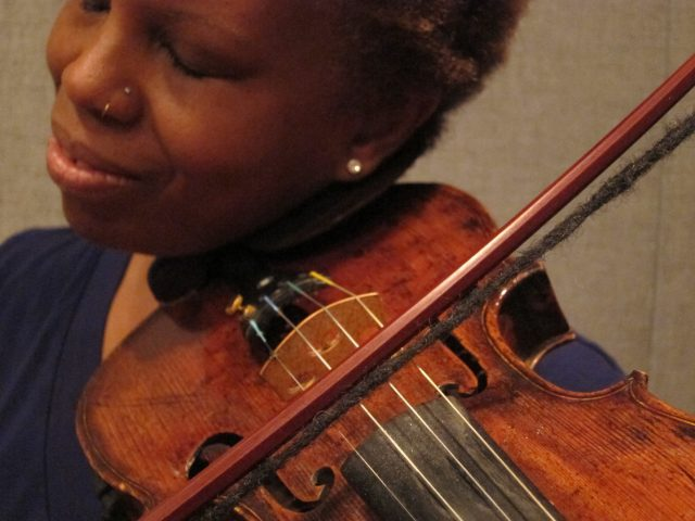 A color photograph of a dark-skinned woman holding a violin and playing its strings with the bow strung from a dreadlock.