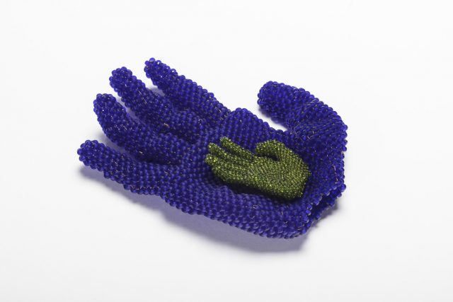 A beaded sculpture of two hands. A larger hand, made of blue glass beads, rests palm up. It cradles a smaller hand made of green glass beads, which is centered in the same position in the larger hand's palm.