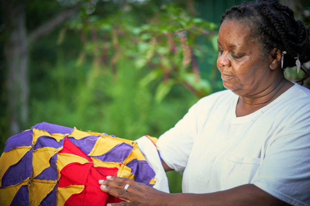 A dark-skinned woman with braided hair worn pinned back holds up a red, purple, and yellow geometric quilt, gesturing to what appears to be it's inseams where the work of the sewing is visible.
