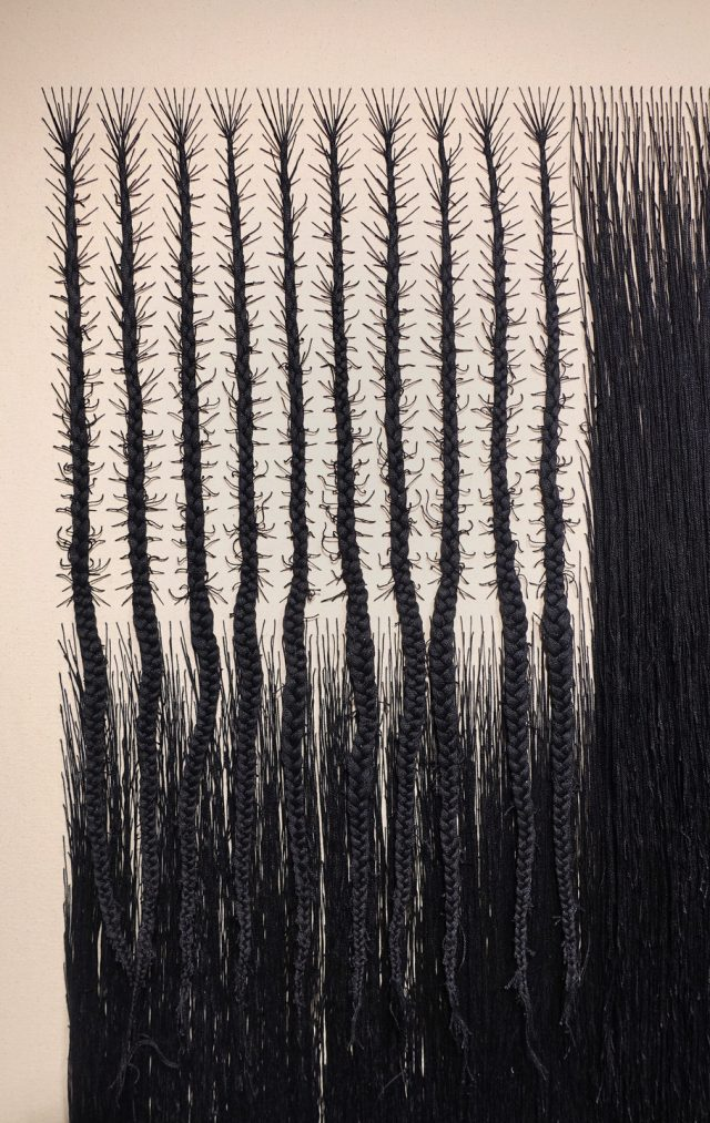 Detail view of a vertical rectangular canvas woven with black cotton thread. The thread has been braided into the approximate form of an American flag. Where the stars would be, the thread forms branching cornrows, and where the stripes would be, the thread hangs densely, like hair.