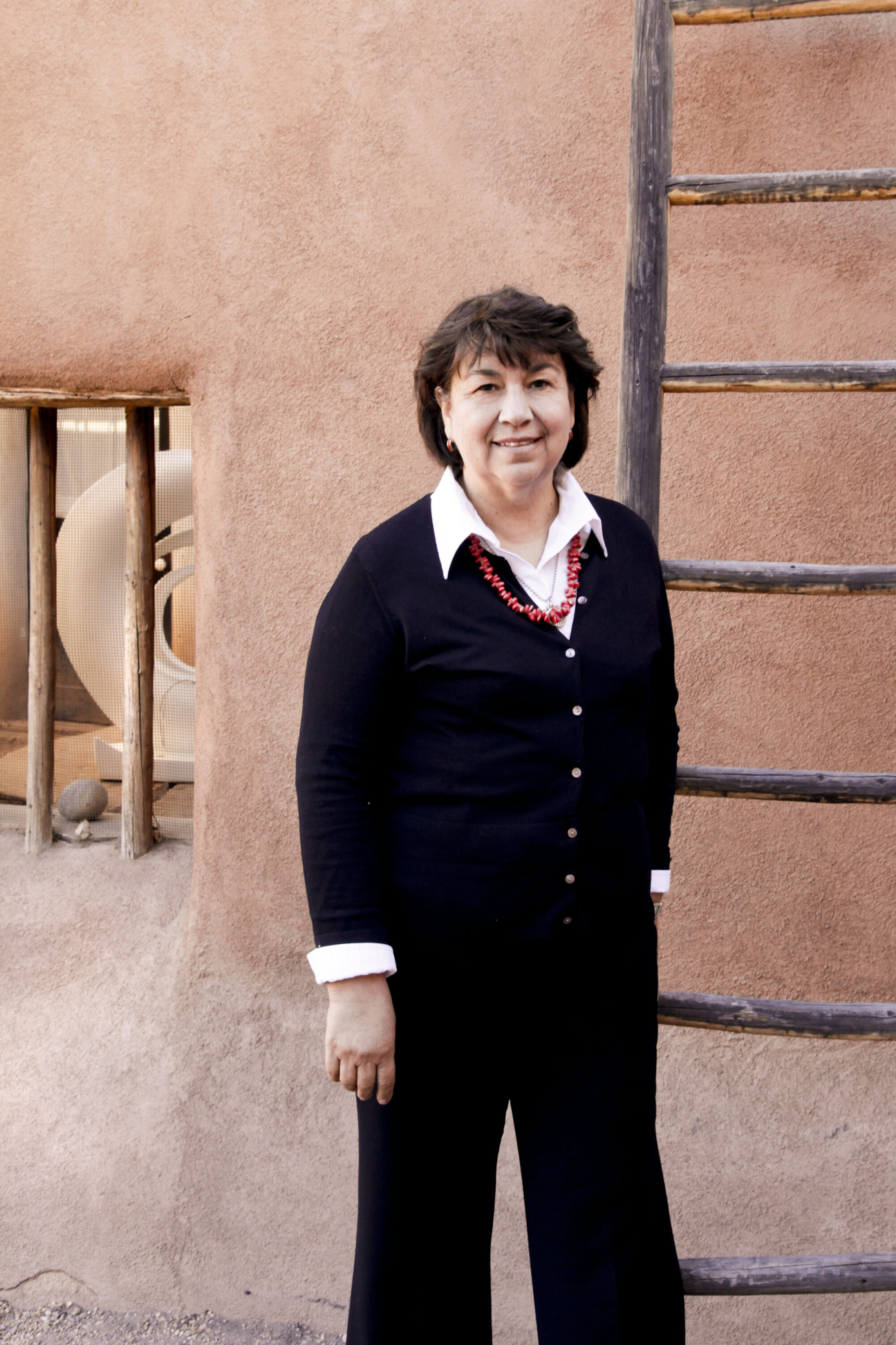 A light skinned woman with short brown hair wearing a black sweater, black pants, a white collared shirt, and a coral necklace, stands smiling in front of a ladder resting against a light pink stucco building. You can see a round white sculpture sitting on a table through the window of the building.
