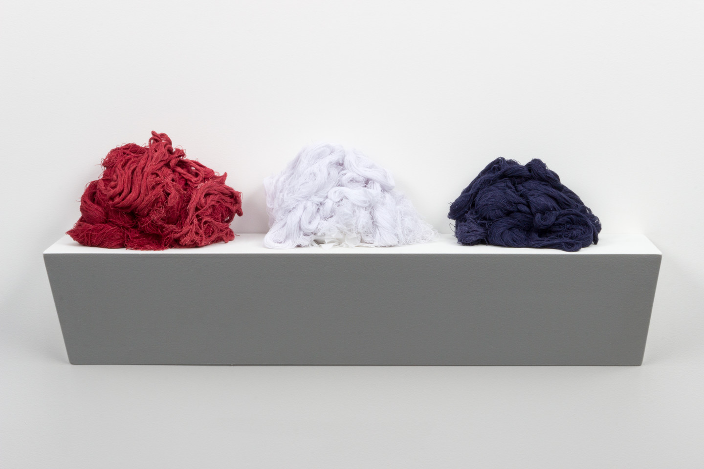 Three piles of thread from an unravelled American Confederate Battle Flag on a white base resembling a shelf. The thread piles are red, white, and blue.