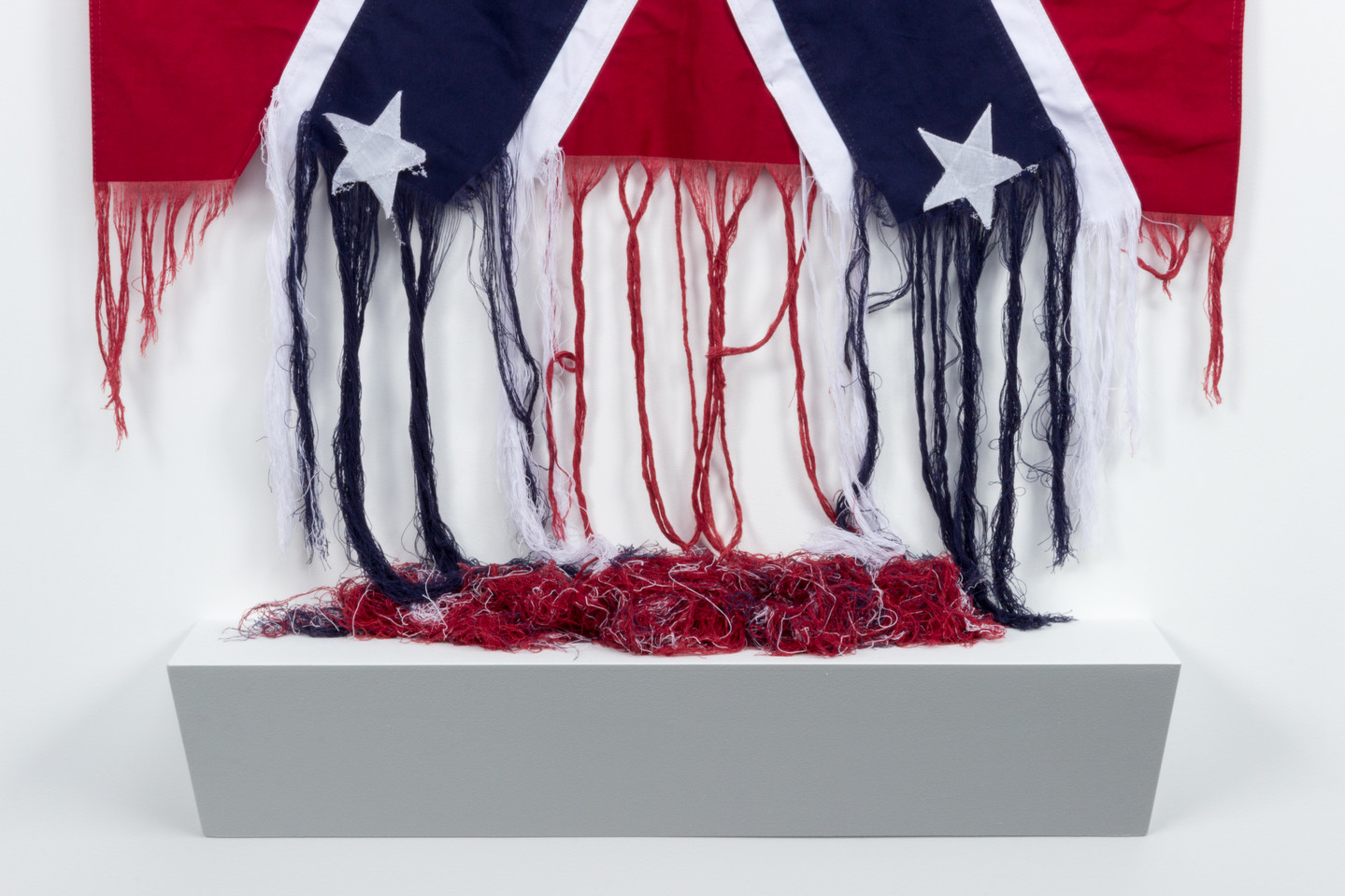 The bottom of an American Confederate battle flag, which has been unraveled. The red, white, and blue threads hang loose, and pool onto a shelf below.