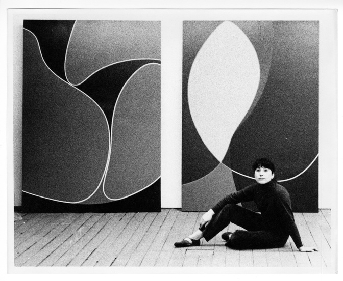 A black-and-white photo of a light-skinned woman sitting on the wooden floor in front of two large abstract works featuring curved lines and soft shapes. She has bangs and wears her hair pulled back and wears a dark turtle neck and dark pants.
