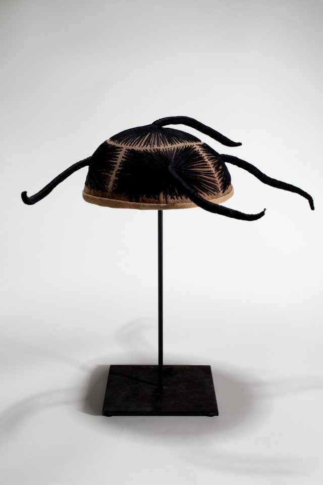 A wig cap sits mounted on a black stand. Black thread is stitched into the cap, mimicking hair. The thread forms five finger-like forms that protrude from all sides.