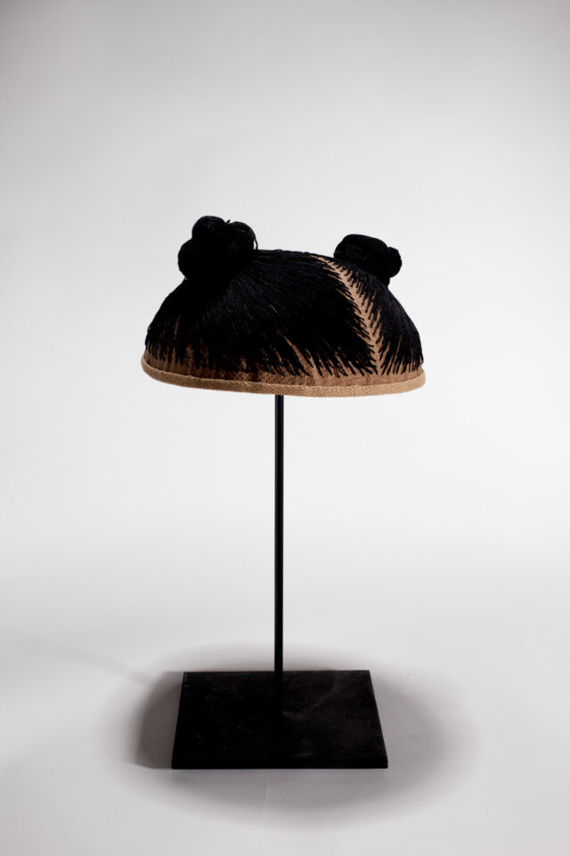 A wig cap sits mounted on a black stand. Black thread is stitched into the cap, mimicking hair. The thread forms two small buns.