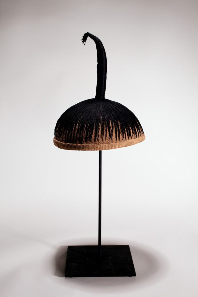 A wig cap sits mounted on a black stand. Black thread is stitched into the cap, mimicking hair. The thread is stitched into a single column, sticking up vertically from the cap.