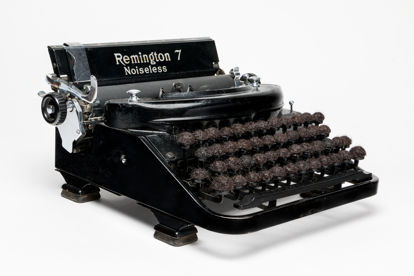 """An antique, black and silver typewriter with the words """"Remington 7 Noiseless"""" emblazoned on the top. The lettered keys of the typewriter have been replaced with balls of dark brown hair."""
