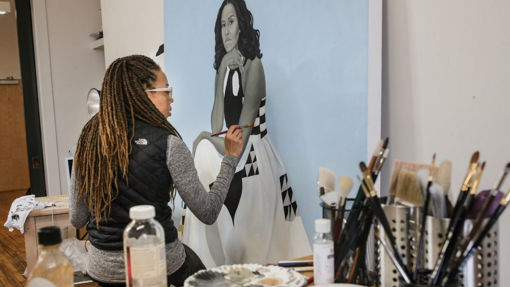 An African American woman with long braids is at work on a painting of Michelle Obama, presented in grey-scale with a powder blue background.