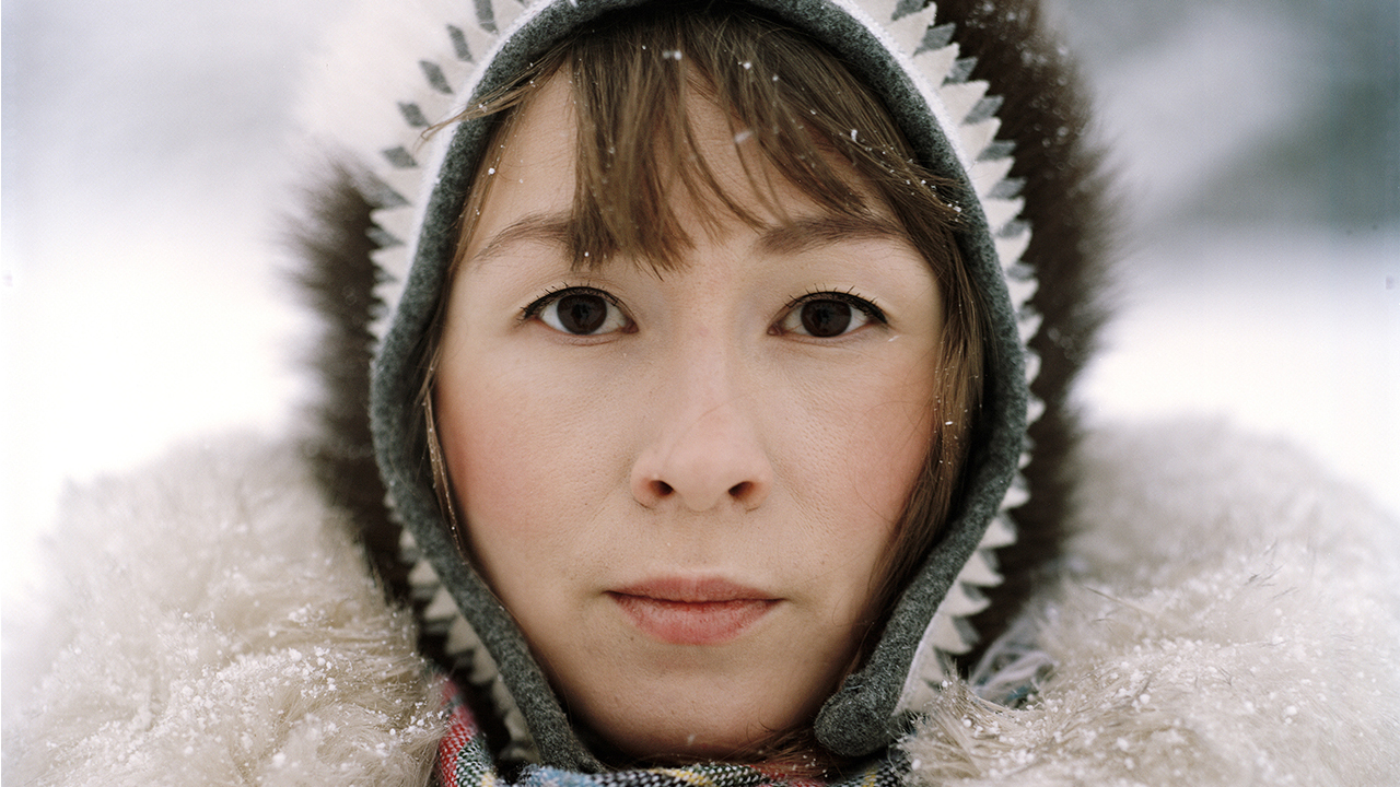 A close-up portrait photograph of a light-skinned woman's face. framed by a fuzzy winter coat hood. On her shoulders and in the blurred background is snow.