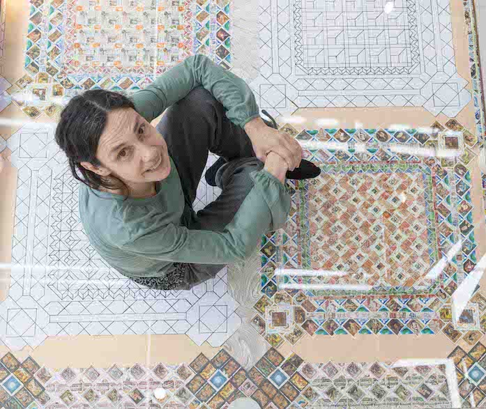 A light-skinned woman sits atop a colorful mosaic floor with her knees drawn up to her chest and her hands clasped on top of them. She looks up at the camera and smiles.