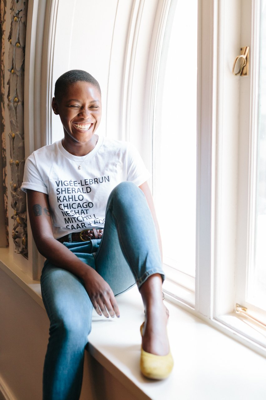 A dark-skinned woman with short cropped hair wears a t-shirt with a list of names of women artists and sits in a large window's sill. She is smiling/laughing and her eyes are closed.