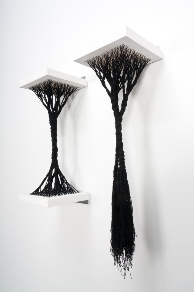 A sculpture made from black cotton thread that has been woven into white canvas shelves. On the left, the thread is affixed tautly between an upper and lower shelf. It has been woven into the canvas in a branch-like formation, and braided as it hangs down. On the right, the thread has been woven into a top shelf, but dangles loosely below.