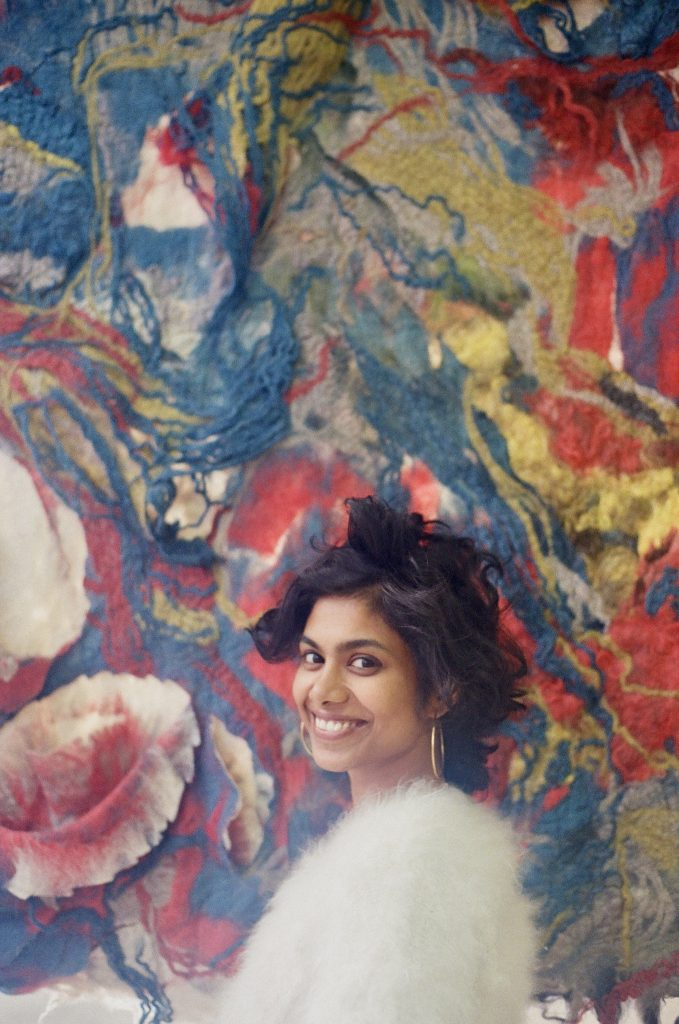 A medium-skinned woman with short wavy black hair stands smiling in front of a large textile work. She wears a white furry sweater and gold hoop earrings.