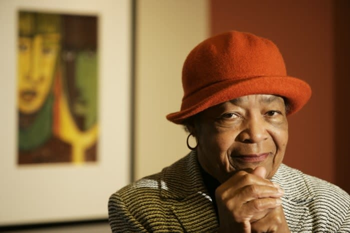 A portrait of a dark-skinned woman who wears a red felt hat, a blazer, and medium-sized hoop earrings. She stares smiling at the camera with both of her hands resting in a fist below her chin. Behind her is an abstract painting, just out of focus.