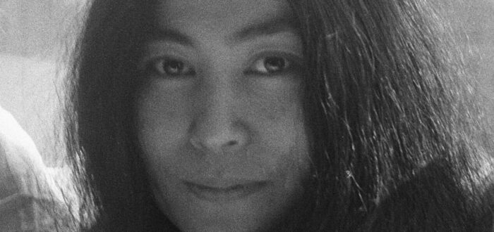 A black-and-white photograph of Yoko Ono in 1969, she wears her black hair long and sits in front of a window. The photo is cropped to her head and she smiles ever so slightly at the camera.