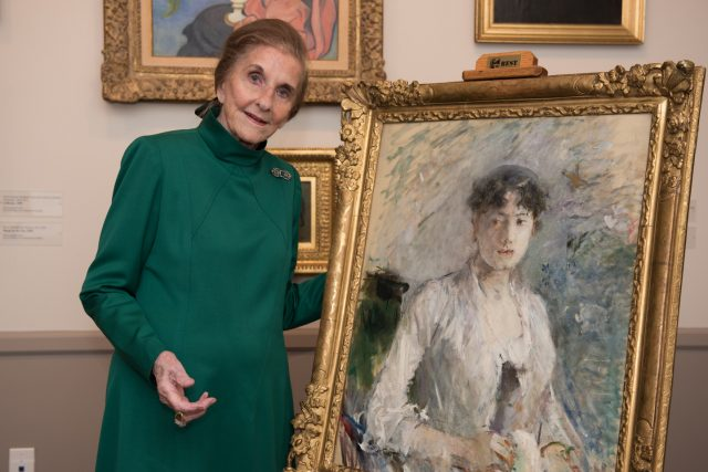 An older light-skinned woman wearing a green dress with a high neck poses next to an impressionist portrait painting of a woman with brown hair. The woman smiles and rests her hand behind the painting's ornate gold frame.