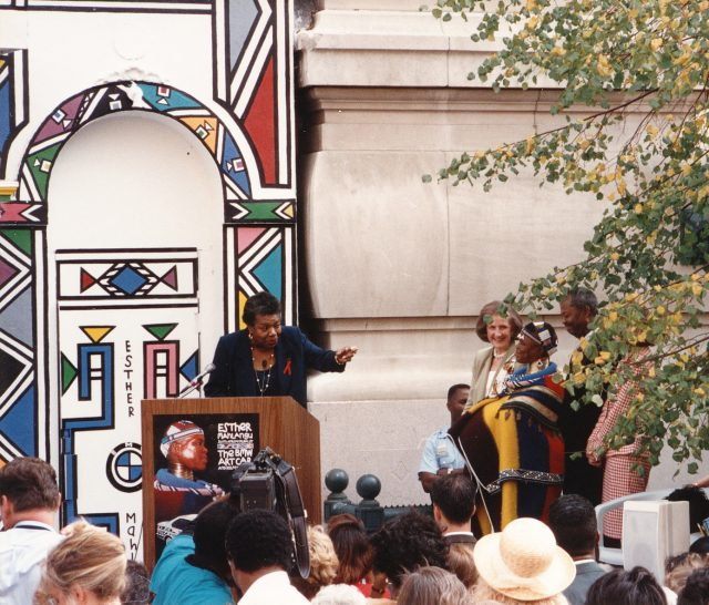 A dark-skinned woman stands at a podium which is set up outside of a large building and in front of a large crowd of people. The woman points to another dark-skinned woman to the right, who is dressed in colorful, traditional African dress and jewelry. She smiles warmly next to a light-skinned woman with shoulder-length brown hair and a dark-skinned man. Behind the podium is a large geometric mural.