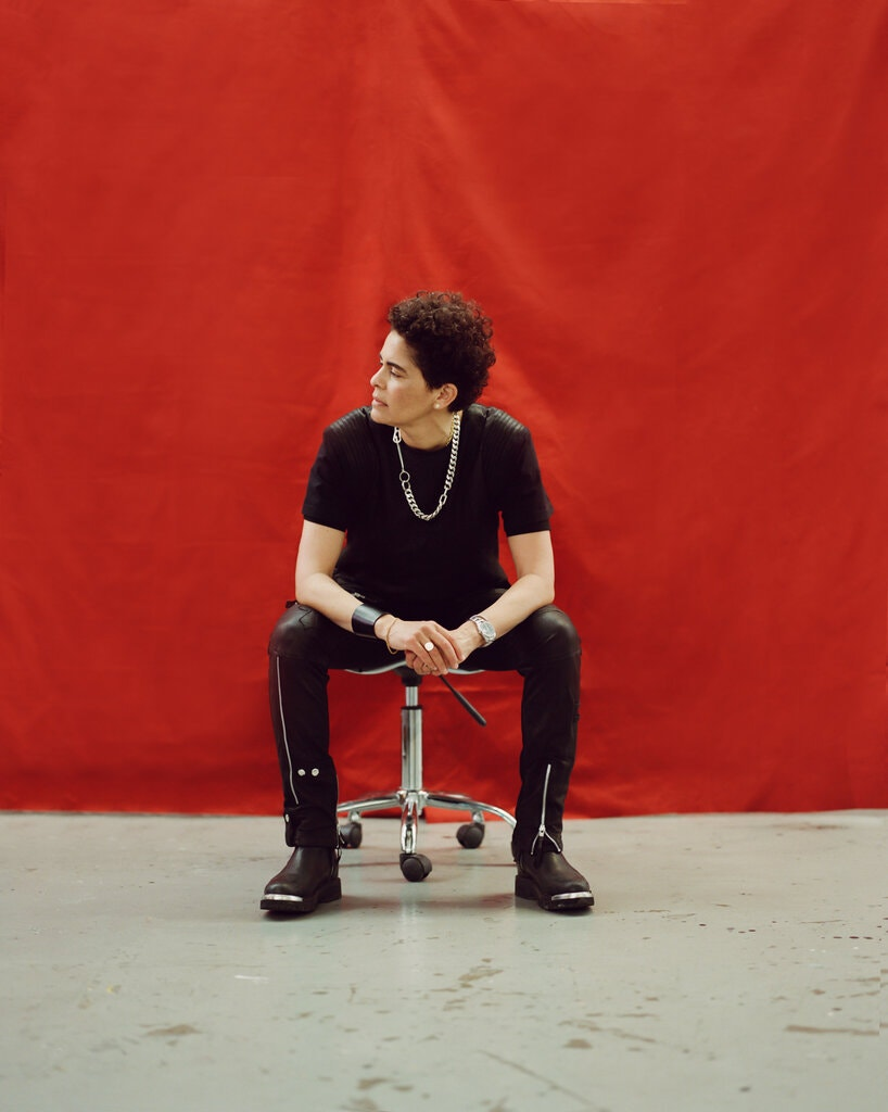 A light-skinned woman wearing a black t-shirt, black pants, and black boots, sits on a roller stool in front of a large red backdrop. Her curly hair is cut short and she looks off to the left, unsmiling.