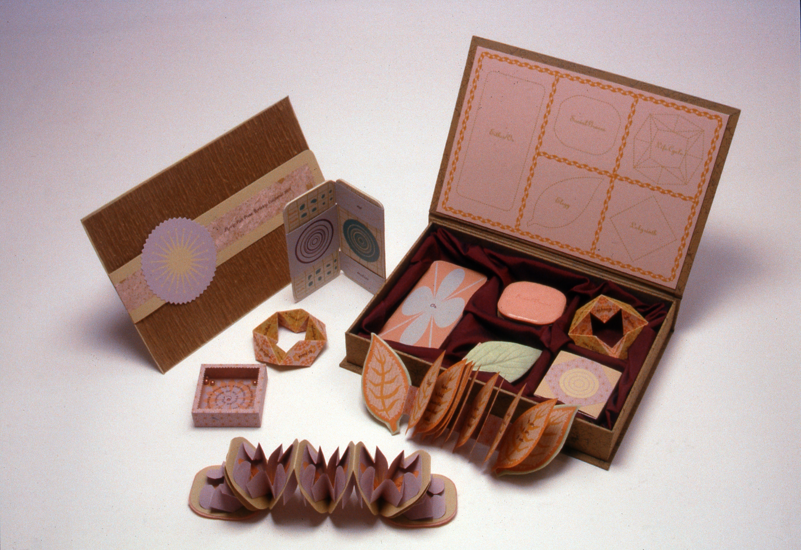 Multiple colorful objects sit spread out against a neutral background, including a rectangular box filled with more small objects, two small books spread open, a small box resembling a game, and other folded paper objects.