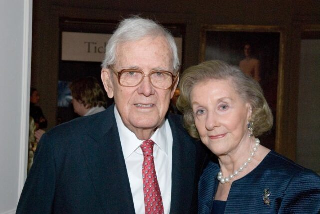 A light-skinned elderly couple smile slightly for the camera, which captures them from the chest up. They are dressed in formal evening attire, the woman wearing large pearls, a broach, and gemstone earrings. The man wears a red patterned tie and glasses.