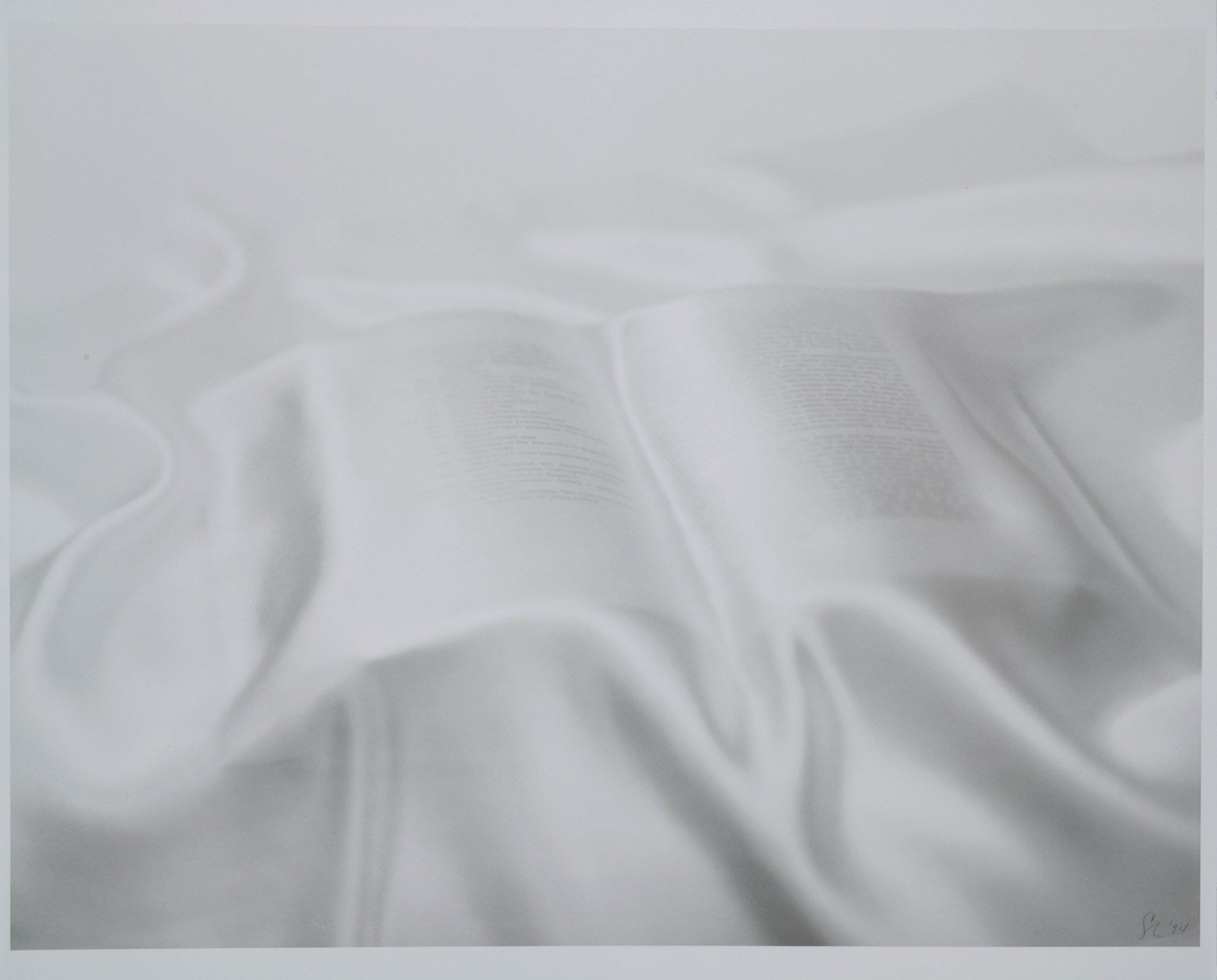 A pure white satin or silk sheet is draped over an open book. Lines of black text is visible through the sheet.