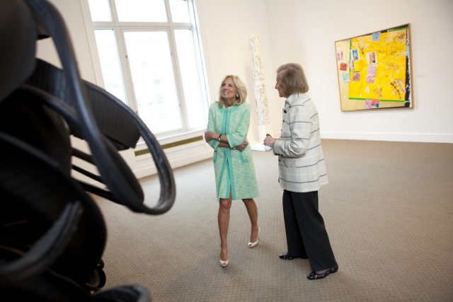 In a large, light-filled gallery, two women look on at a wall sculpture that is made of black shredded tires. The woman on the left wears a turquoise blue skirt and jacket set with white open-toed heels. She smiles looking on at the artwork. The women on the right is older and dressed in black pants and a white and grey striped over coat. The appear mid-conversation.