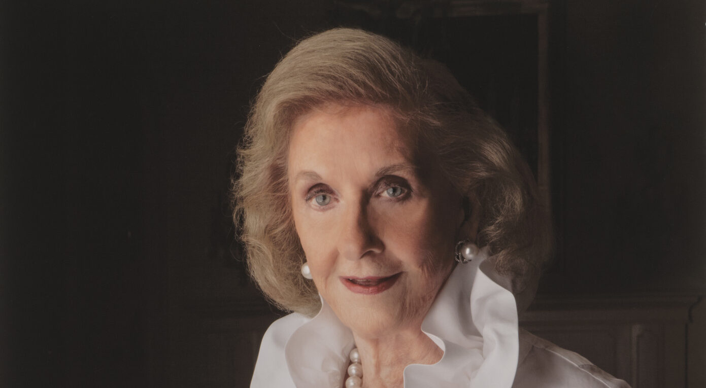 Professional portrait of a light-skinned, older woman with a blonde bob. She wears an elegant white ruffled blouse and pearl jewelry.