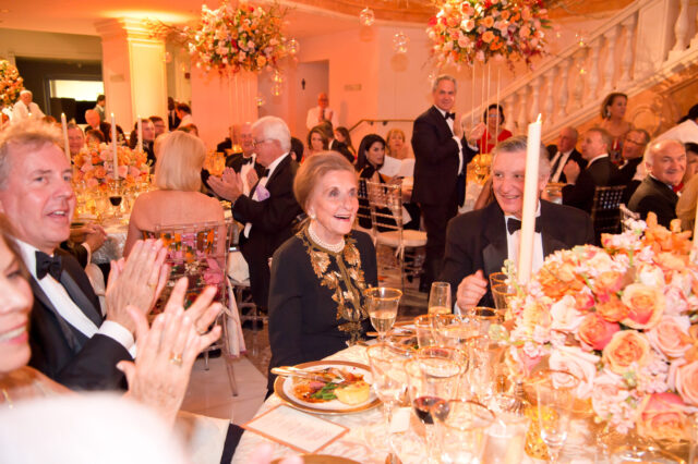 An older light-skinned woman is celebrated during a gala dinner. Many guests sit in the seats and turn towards her clapping. She smiles happily. Large, ornate bouquets decorate the hall and are the centerpieces of the tables.