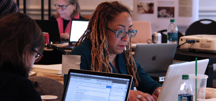 A woman with ombré dreadlocks sits at a table working on her laptop. Two other women are doing the same thing at different tables directly behind and in front of the woman.