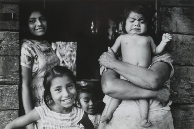 A black and white photograph of women and children standing in a wooden doorway. A figure whose head and face are obscured holds a baby, who is crying. Next to her stands a woman who leans against the doorframe, smiling. In the lower part of the frame are two young girls. The one in the foreground smiles broadly, her dark hair pulled back from her face.
