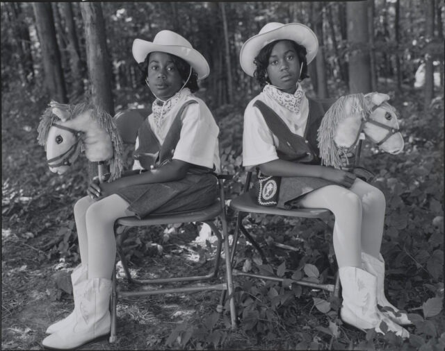 A black-and-white photograph of two dark-skinned young twins sitting in folding chairs against a woodsy background, facing the camera with their bodies angled outward in opposite directions. They wear matching cowgirl outfits, complete with hats, boots, and hobby horses.