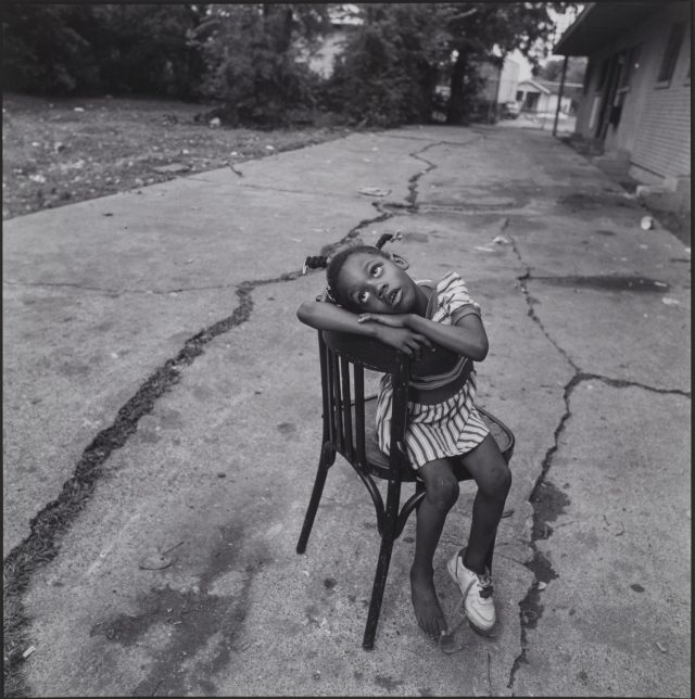 A black-and-white photograph of a dark-skinned young girl sitting sideways in a chair on a cracked street. She has braids and wears a striped dress and one sneaker. Her arms rest atop the back of the chair, and her head rests sideways on top of her arms as she looks skywards.