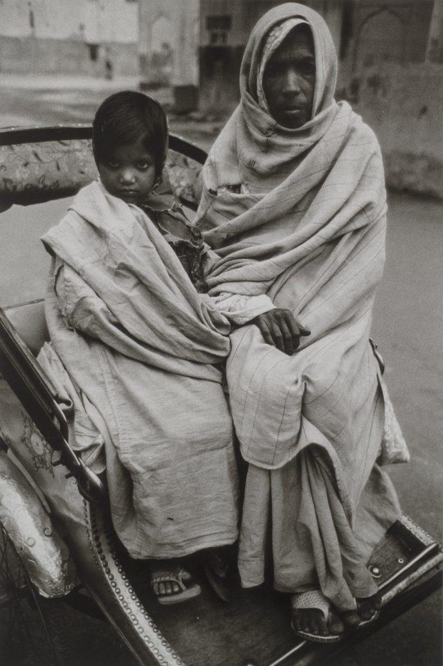 A black and white photograph of a young girl and older woman sitting side by side in a wheeled cart. The young girl has dark hair, which is pulled back, and she is wrapped in a light colored blanket. The older woman is wrapped entirely in a light colored blanket from her ankles to her head. Her hair and body are not visible. They both stare directly into the camera with serious expressions.