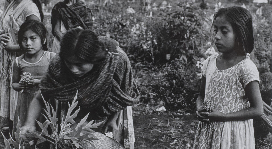 A black and white photograph of women and children preparing a grave in the dirt outdoors. An adolescent girl stands to the side observing. She wears a light colored, patterned dress, and her dark hair is pulled back into a low ponytail. To her right, a woman with dark hair and a dark shawl leans down over a plant. Five other figures stand near her.