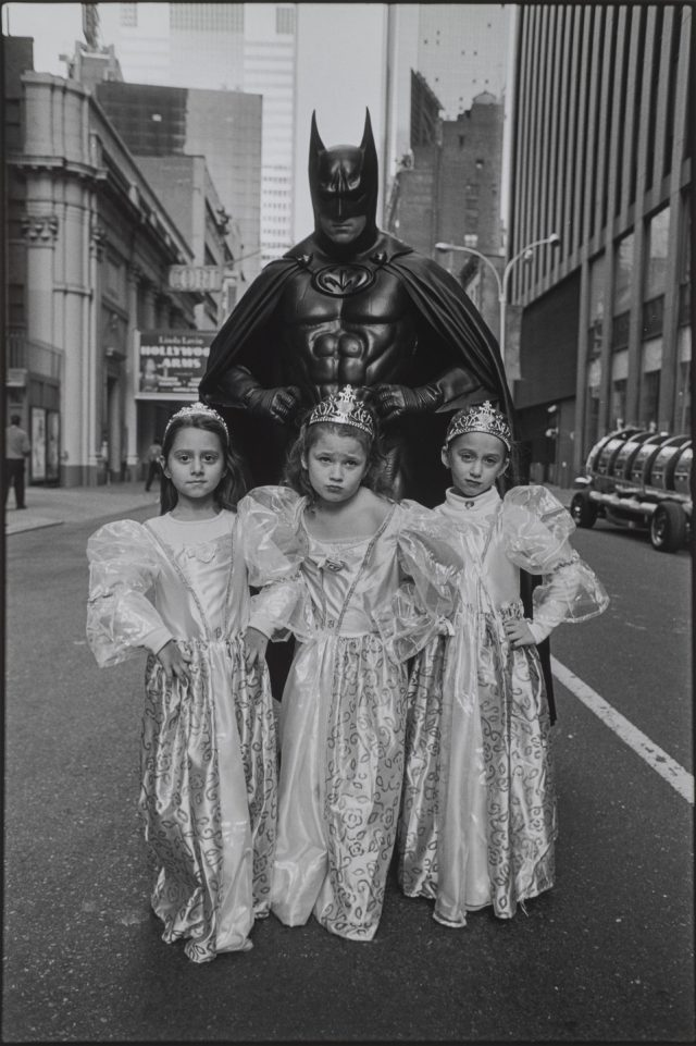 A black-and-white photograph of three light-skinned young girls in princess costumes of dresses and crowns standing in front of an adult in a full Batman costume. They all stand in the middle of a city street with defiant poses, their hands on their hips and faces serious.
