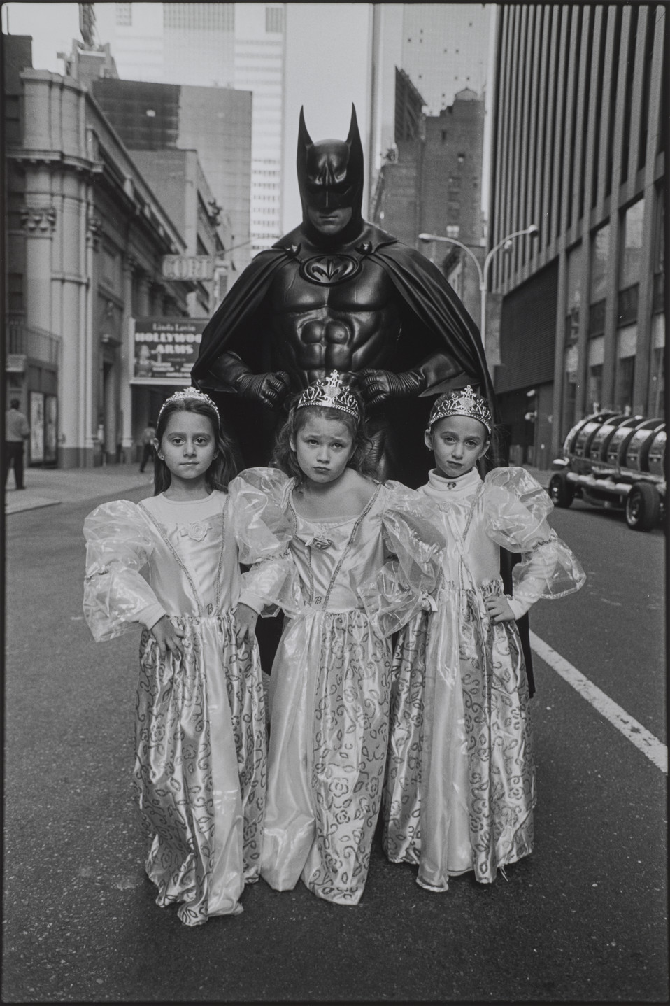 A black and white photograph of three young girls wearing matching princess dresses and crowns standing in front of a tall figure dressed in a Batman costume. All four stand in the middle of the street in a city setting, surrounded by buildings. The girls are posed with their hands on their hips and serious expressions.