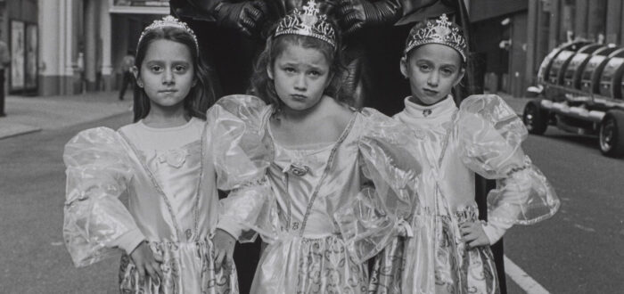 A black and white photograph of three light skinned young girls wearing princess dresses and crowns standing in front of a person wearing a full Batman costume. The three girls stand in defiant poses with their hands on their hips and serious expressions. The background is a city setting.