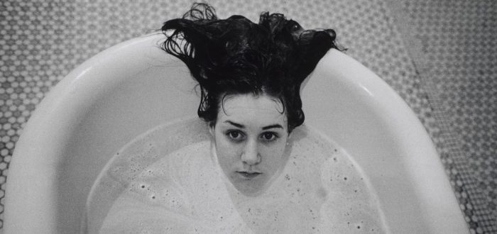 A black-and-white photograph of a light-skinned girl submerged in a white bathtub. Only her head is visible above the soap suds, and her dark hair hangs over the side of the tub. The floor beneath the tub is tiled.