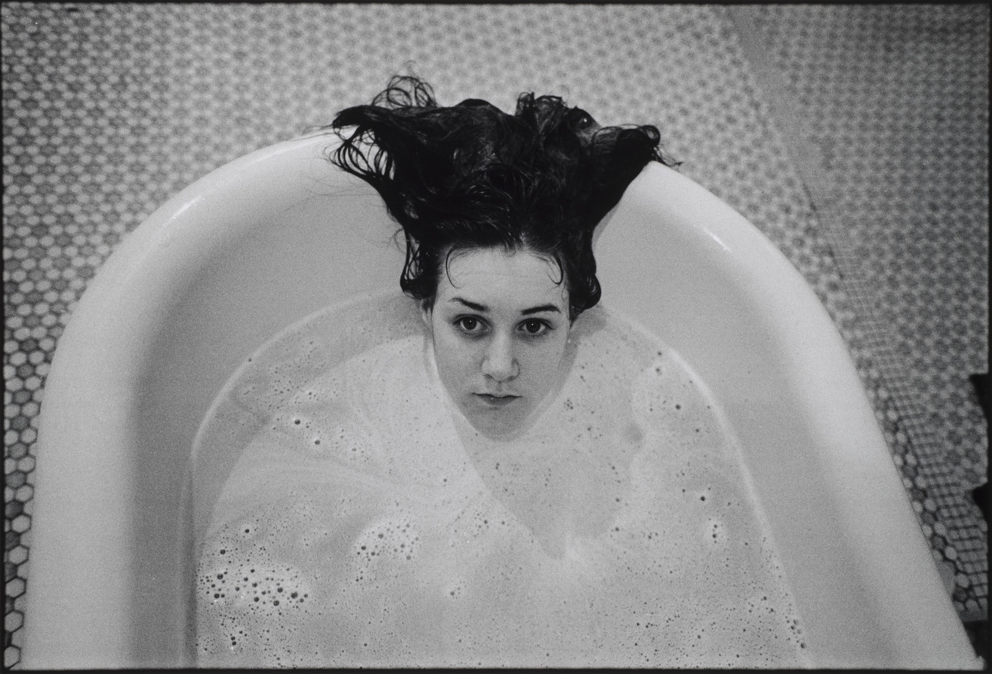 A black and white photograph of a girl submerged in a white bathtub. Only the girl's head is visible above the soap suds, and her dark hair hangs over the side of the tub. The floor beneath the tub is tiled.